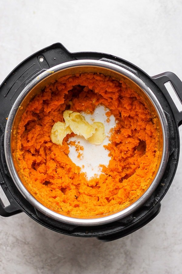 Cooked sweet potatoes with coconut milk, salt, and ghee that are starting to be mashed.