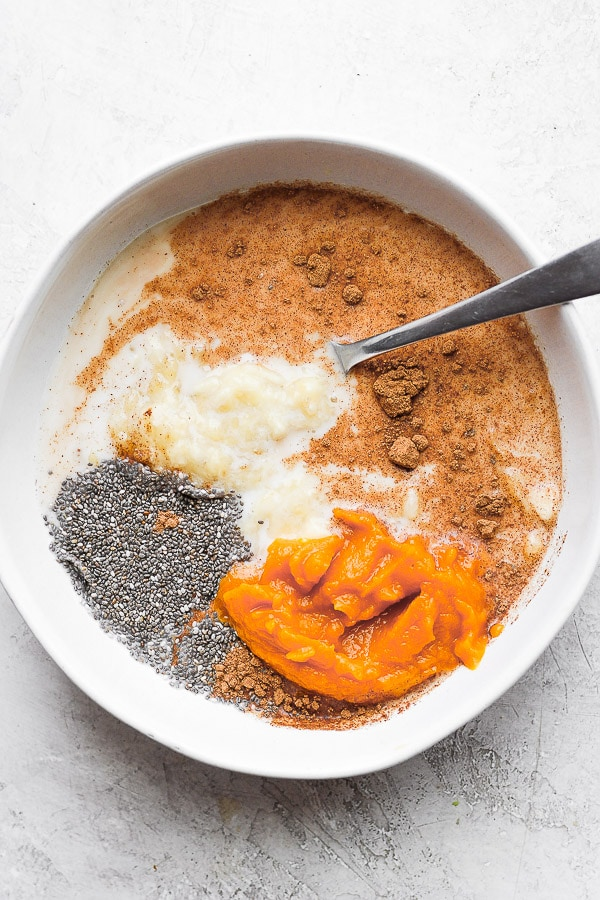 Pumpkin overnight oat ingredients in small bowl with spoon sticking out.