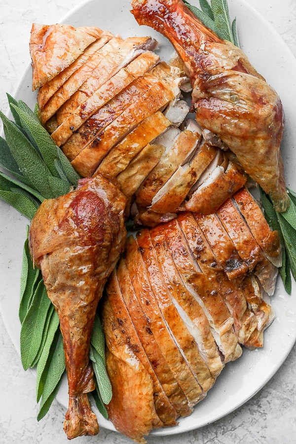 Carved turkey on a platter with fresh sage.