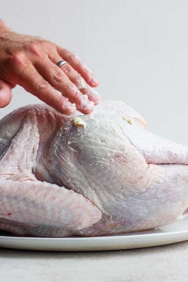 Male hand rubbing butter on raw turkey.