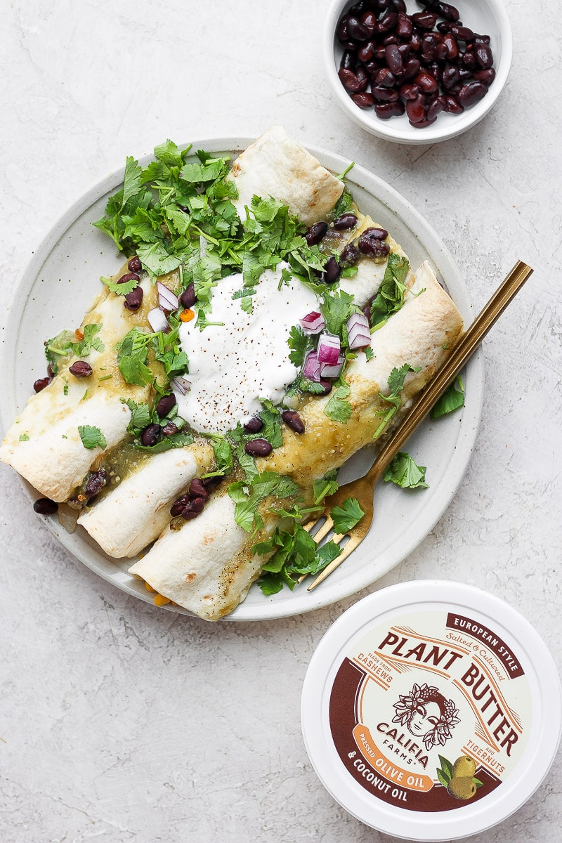 A plate with three vegan enchiladas topped with fresh cilantro, dairy free sour cream and red onions.