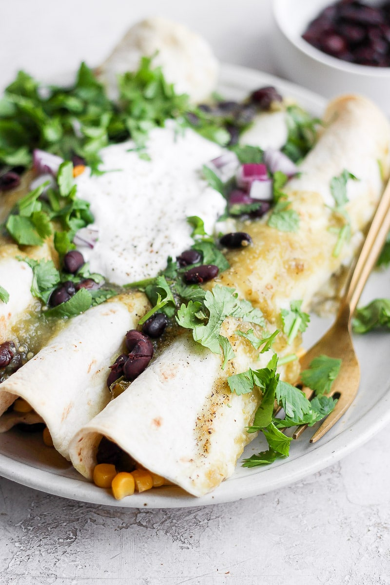 Side angle of a plate with three vegan enchiladas topped with fresh cilantro, dairy free sour cream and red onions.