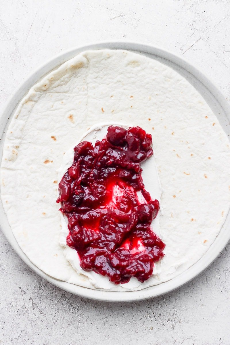 A tortilla with dairy-free cream cheese and cranberry sauce.