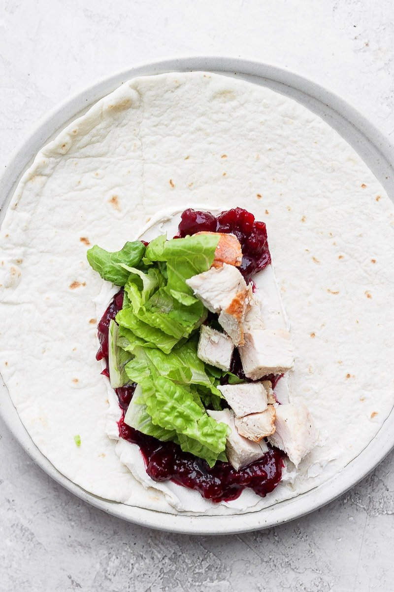A tortilla with cranberry sauce, dairy-free cream cheese, romaine lettuce, and turkey.