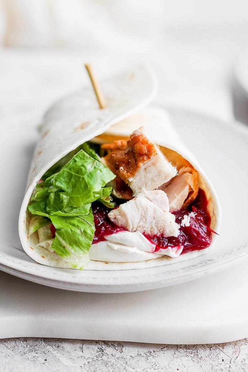 A turkey cranberry wrap on a white plate.
