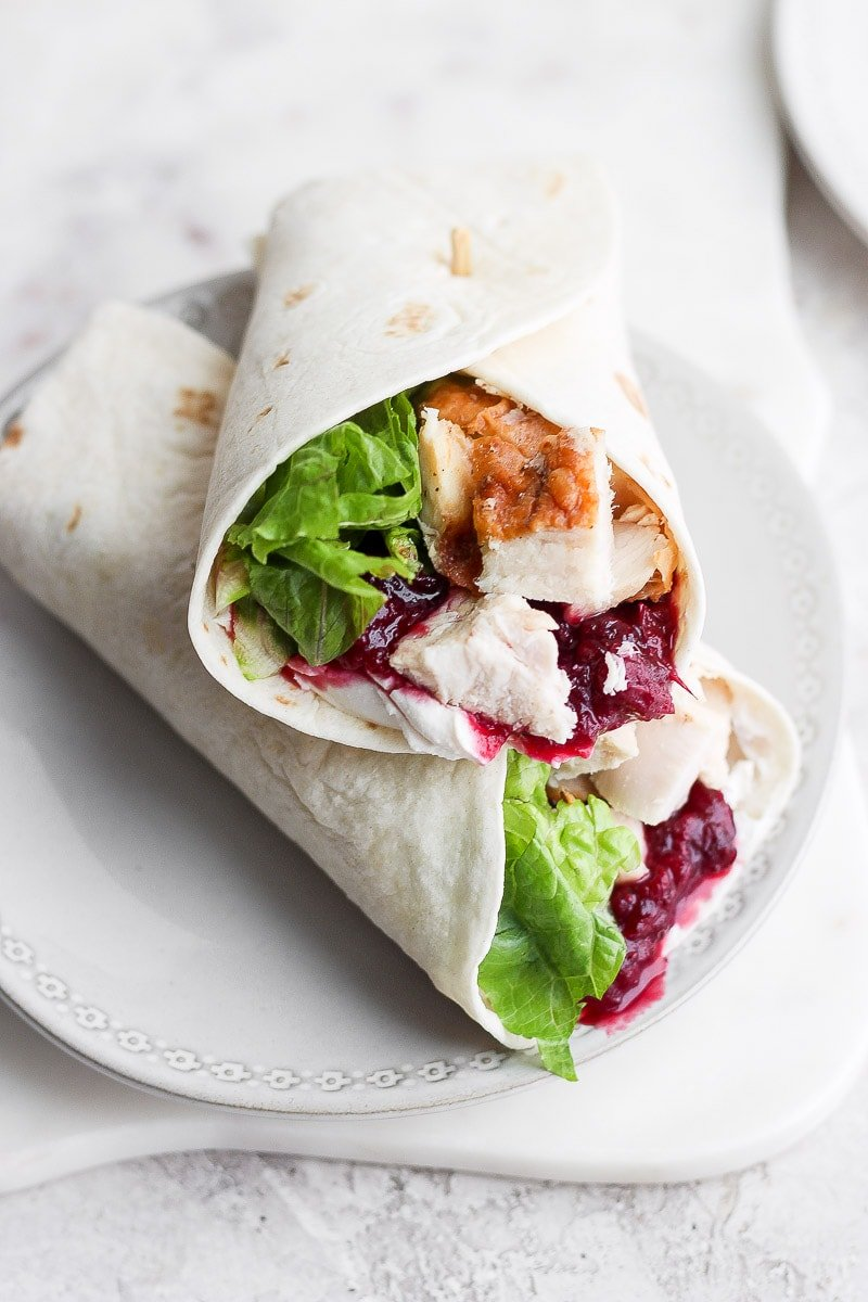 2 turkey cranberry wraps stacked on a white plate.