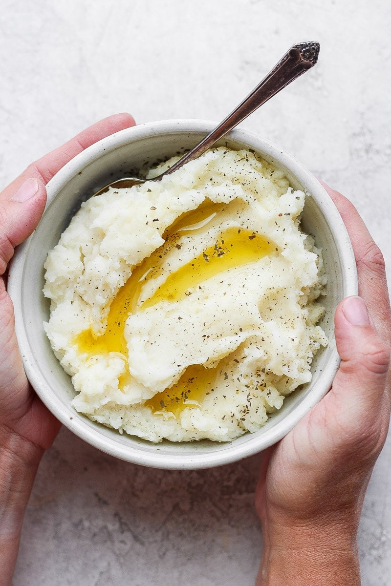 Hands holding a bowl of mashed potatoes with melted ghee, salt, pepper, and a spoon.