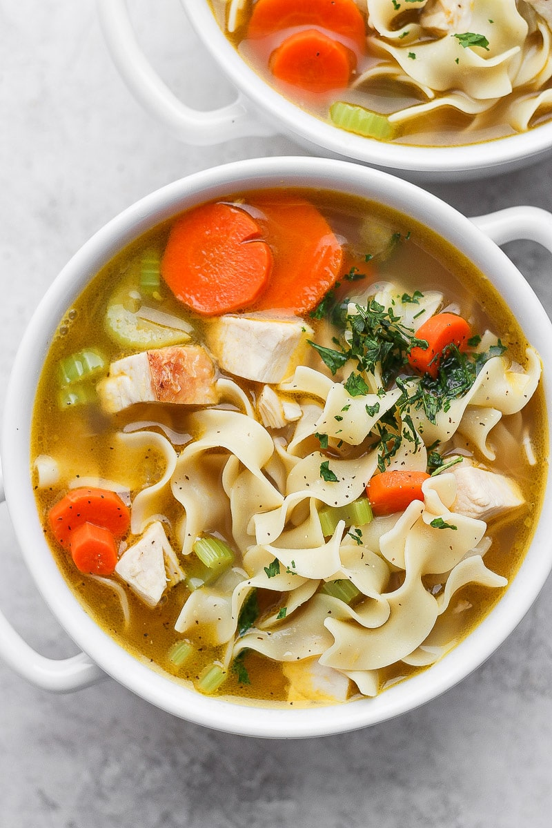 A white bowl with homemade turkey noodle soup.