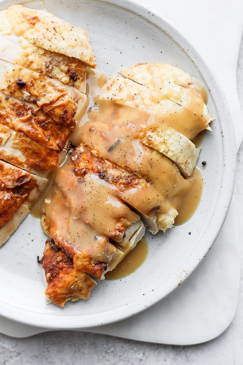 Plate with sliced chicken breast covered in chicken gravy.