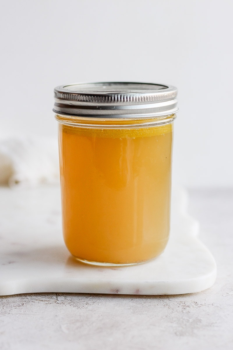 A mason jar full of homemade chicken broth.