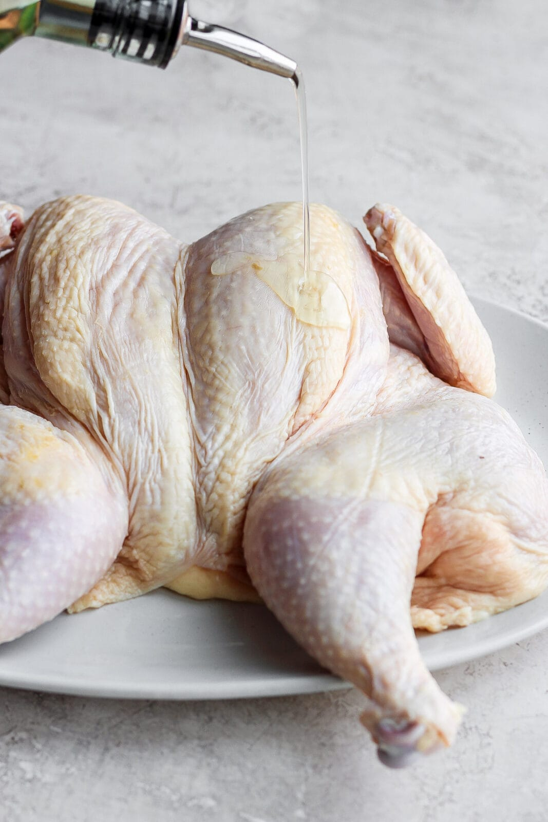 Pouring oil onto a spatchcocked chicken.