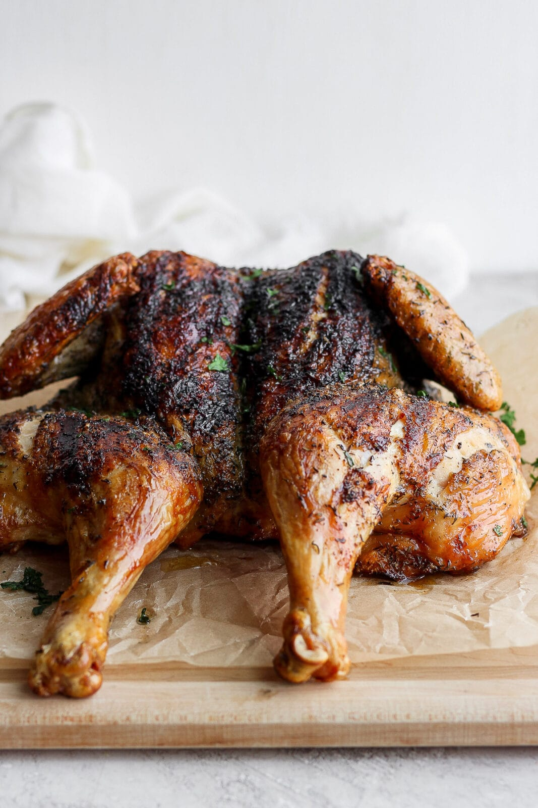 A whole, spatchcock chicken on a cutting board and parchment paper.