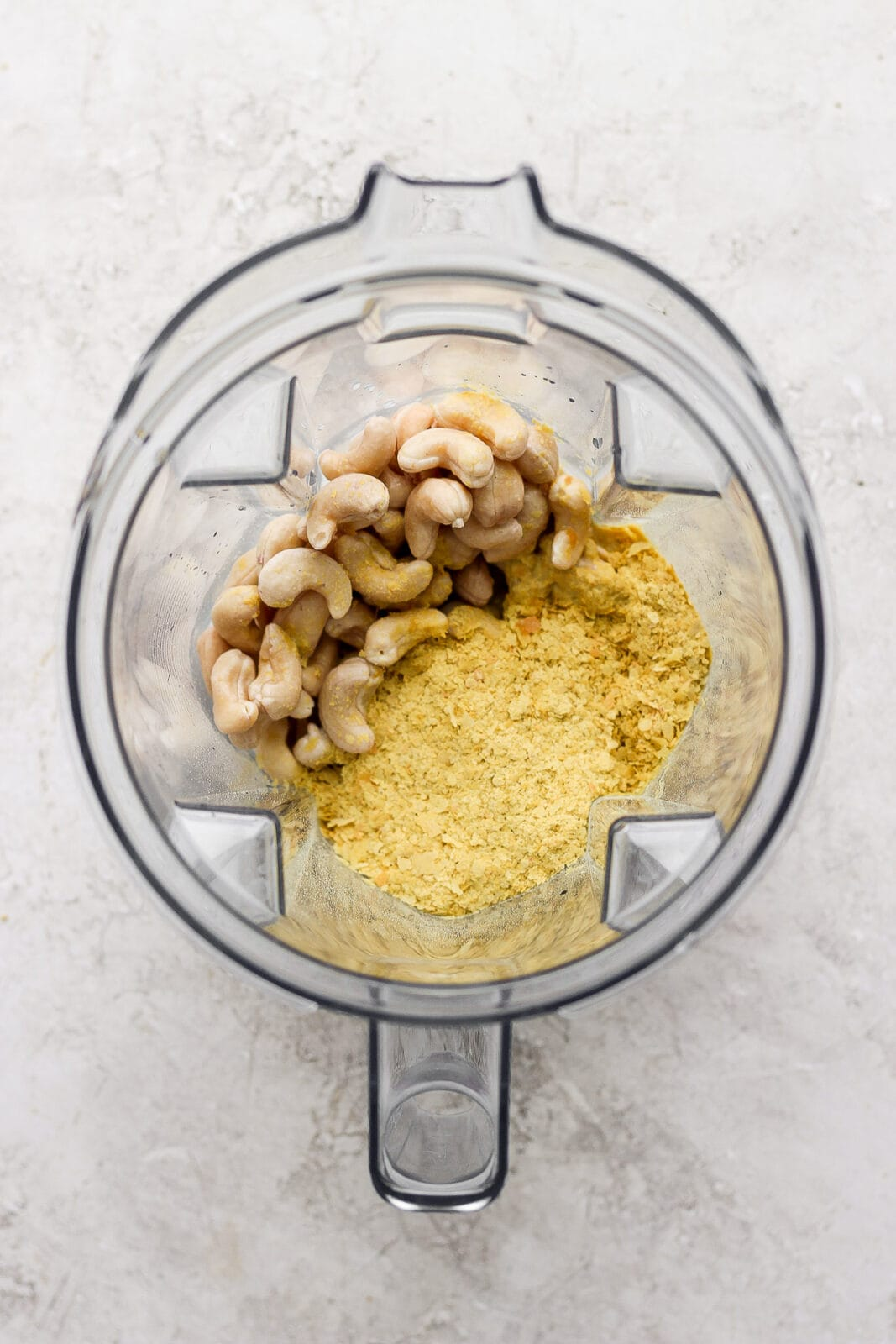 Top shot of blender filled with drained cashews and nutritional yeast.
