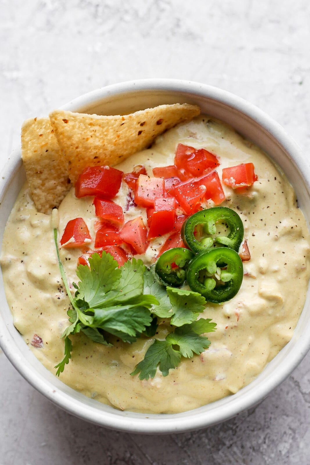 Bowl of vegan queso dip topped with fresh tomato, japaleno and cilantro.