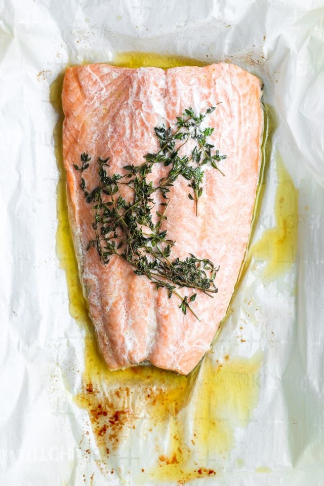 Parchment paper with a cooked fillet of salmon, melted ghee, and thyme.