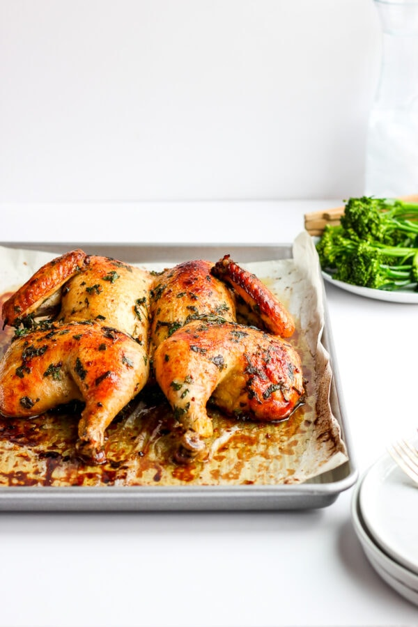 Pan with a baked, butterflied chicken and a plate of broccolini in the background.