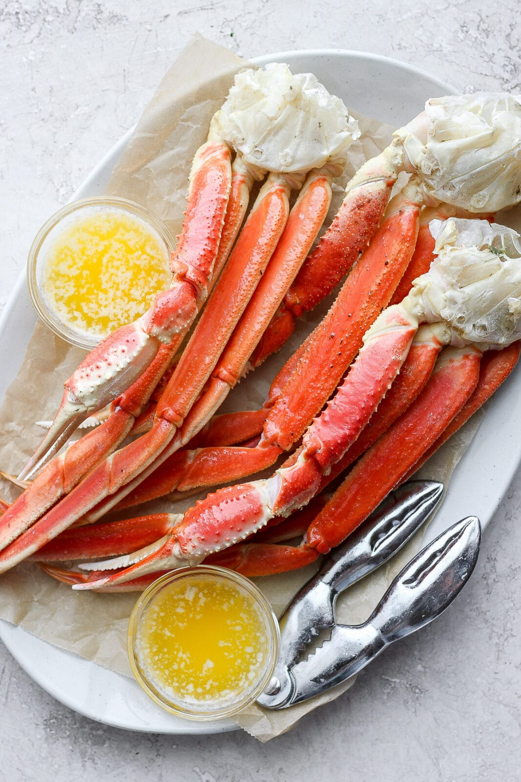 Plate of baked crab legs with little bowls of ghee next to them.