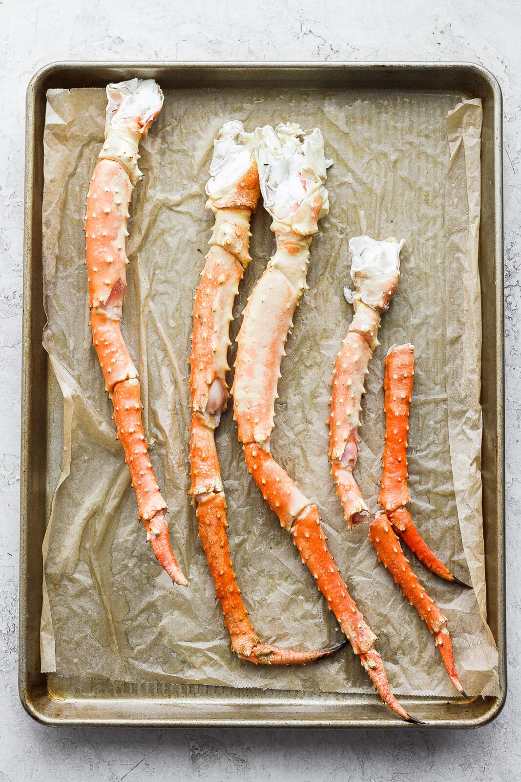 Parchment paper lined baking sheet with king crab legs on top.