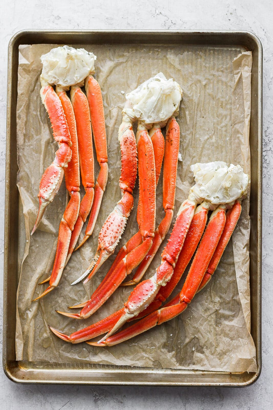 Parchment lined baking sheet with show crab clusters on top.