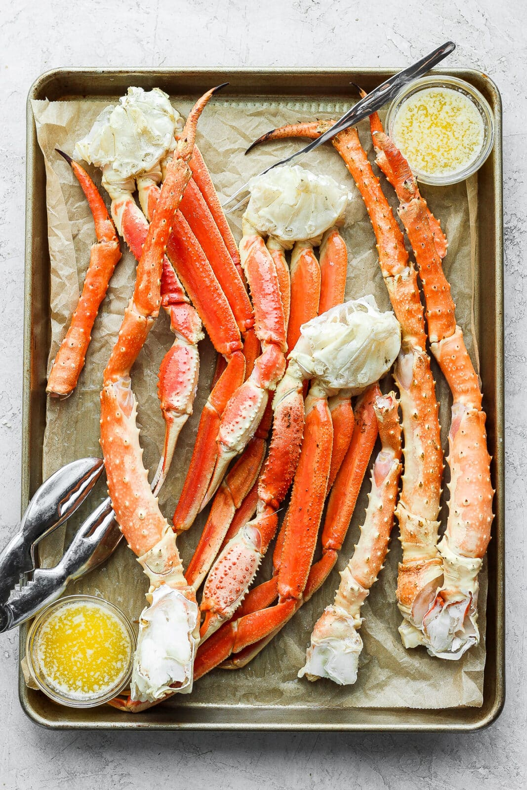 Parchment lined baking sheet filled with show crab and king crab legs as well as some bowls of ghee.