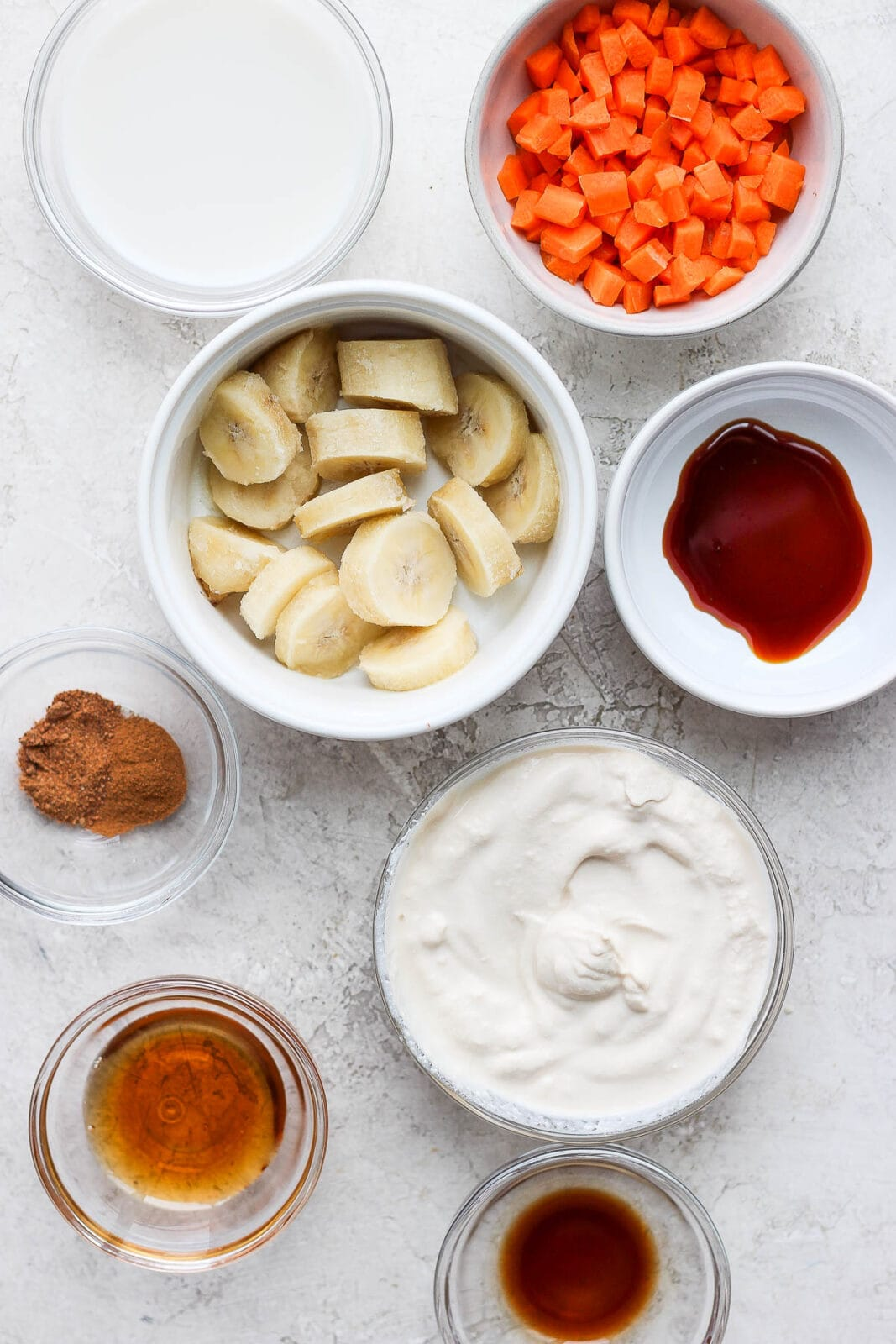 Ingredients for carrot cake smoothie separated in white bowls.