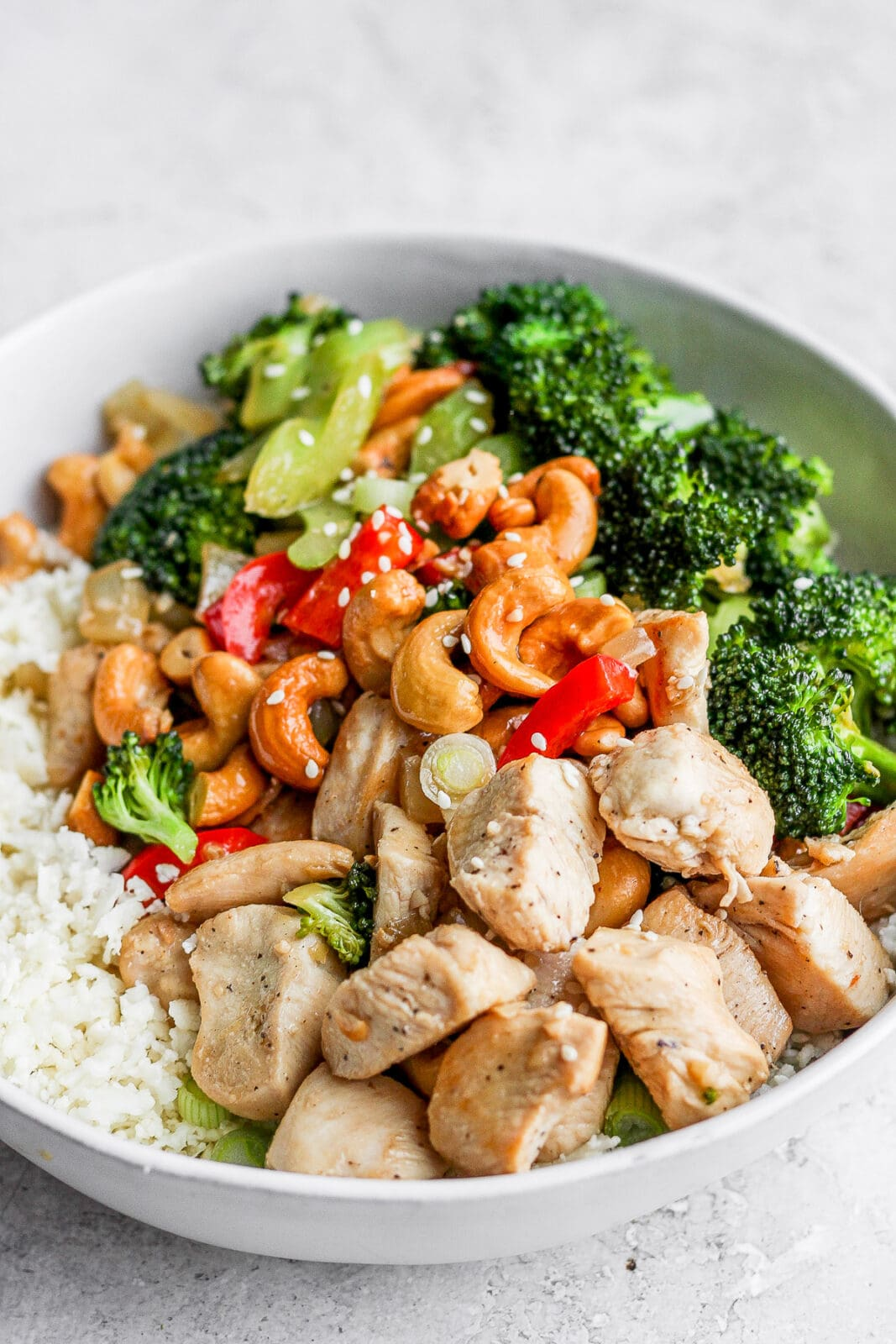 Close-up view of cashew chicken stir fry on cauliflower rice.