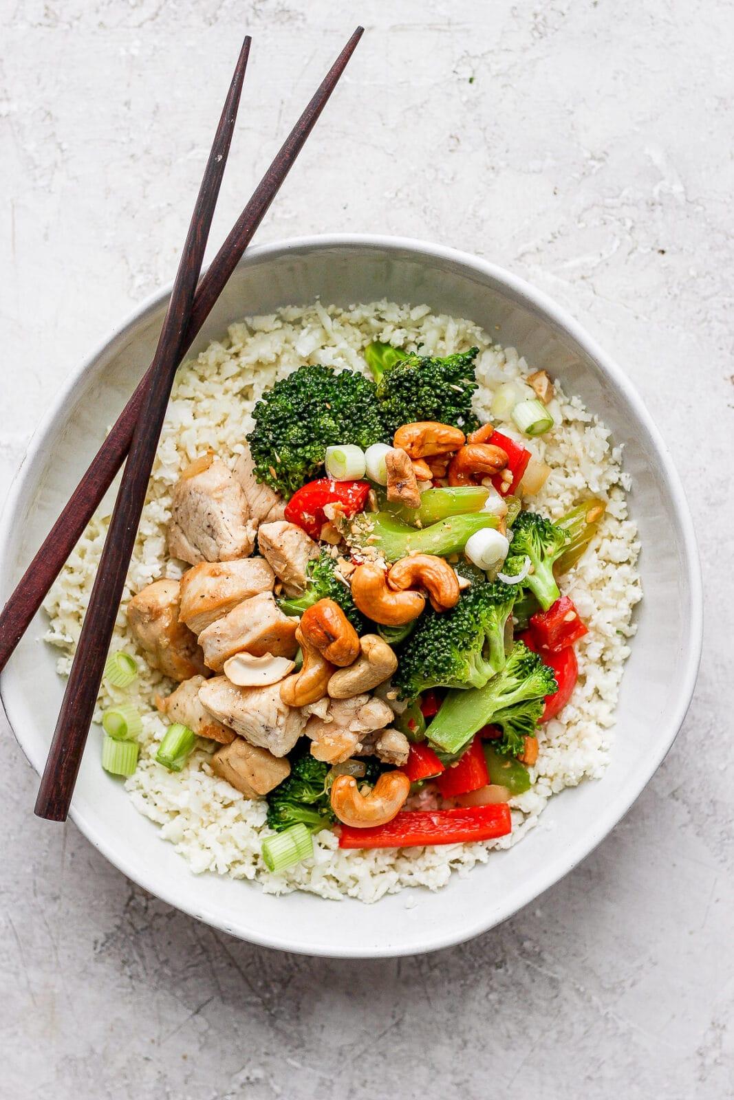 Bowl of cashew chicken stir fry on cauliflower rice with chopsticks.