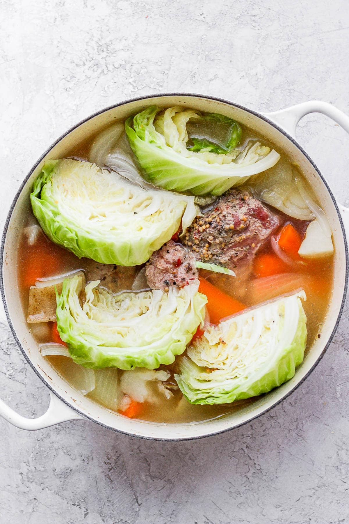 Dutch oven filled with corned beef and cabbage.