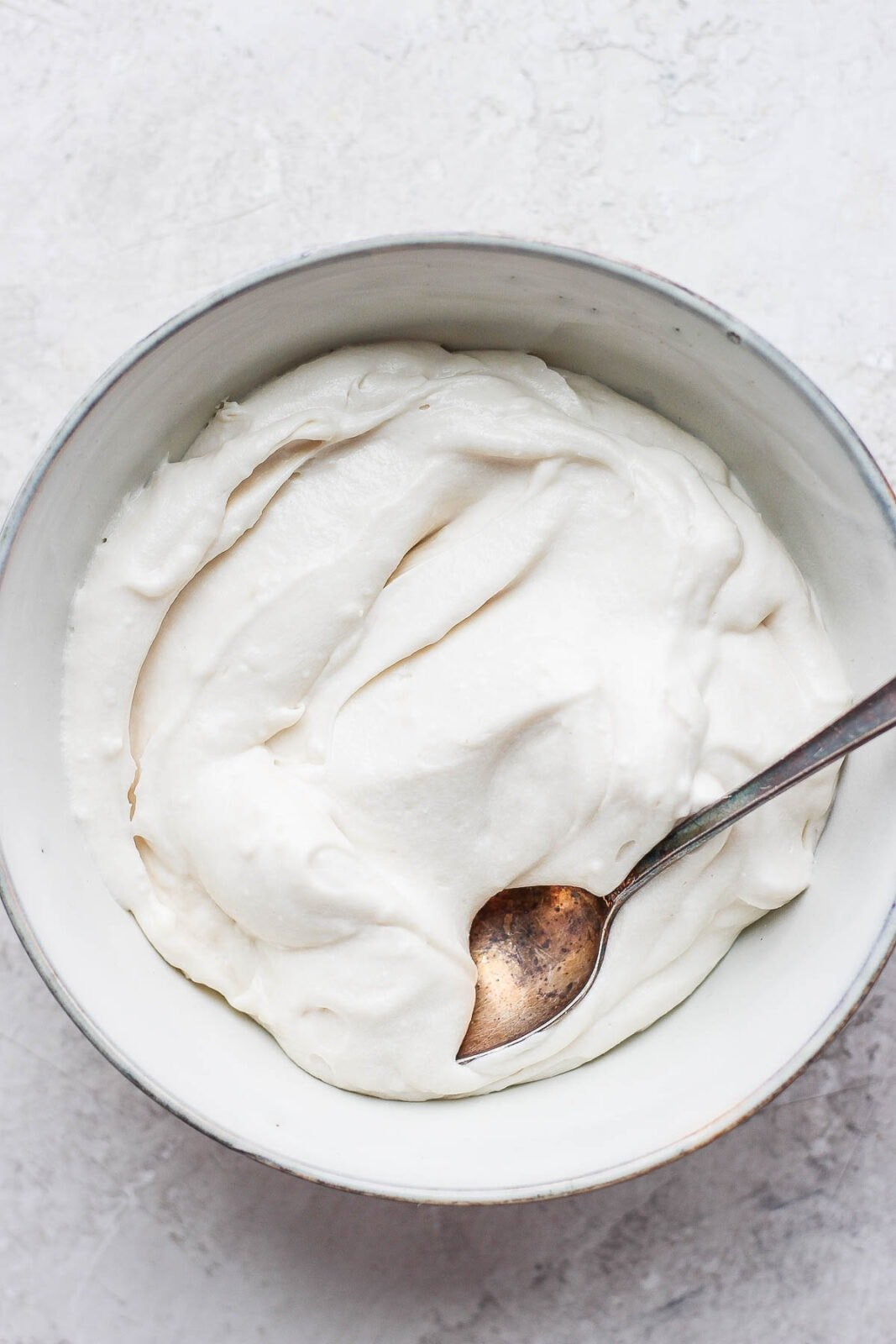 Bowl of dairy free cream cheese frosting and a spoon.