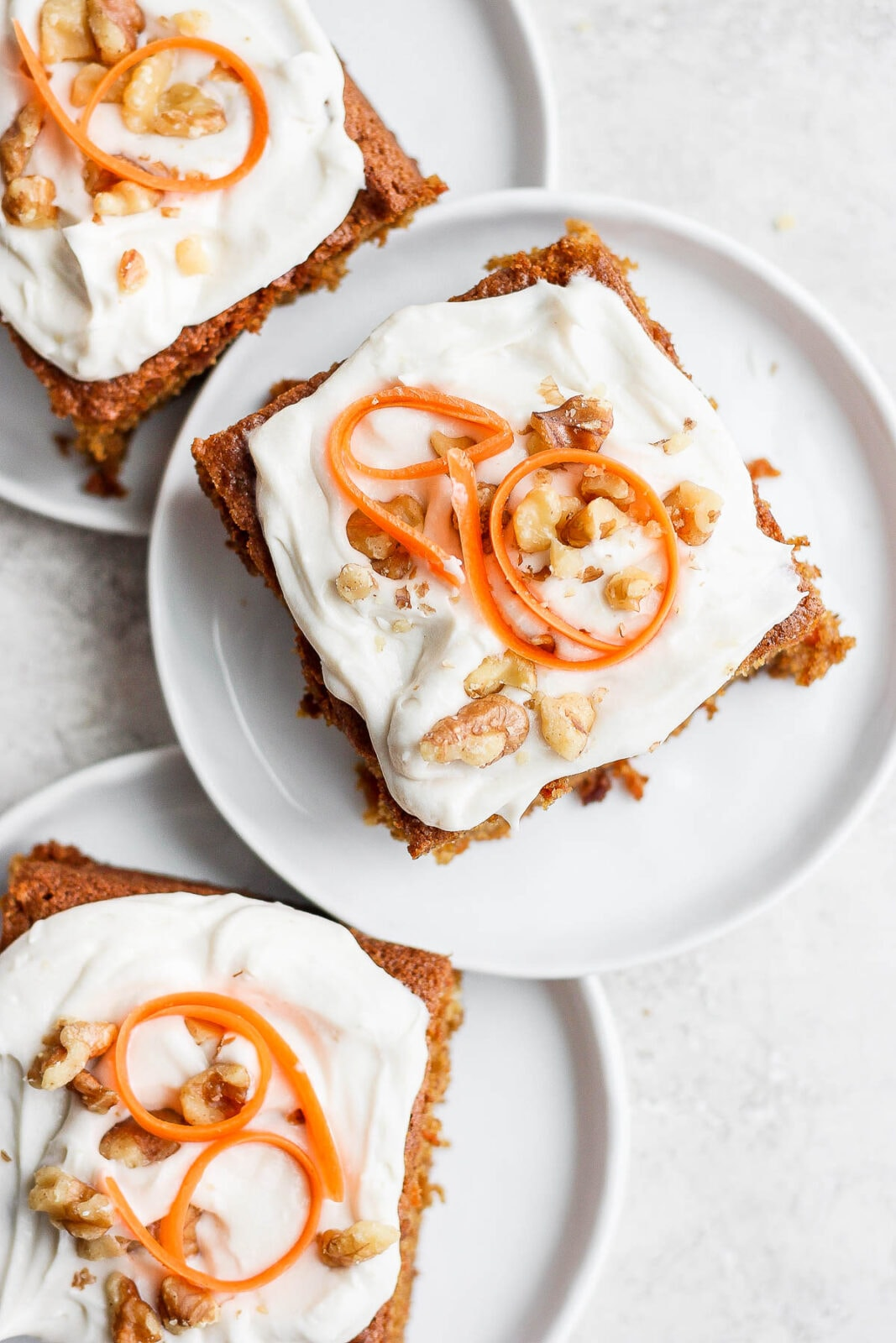Three slices of gluten free carrot cake on plates.