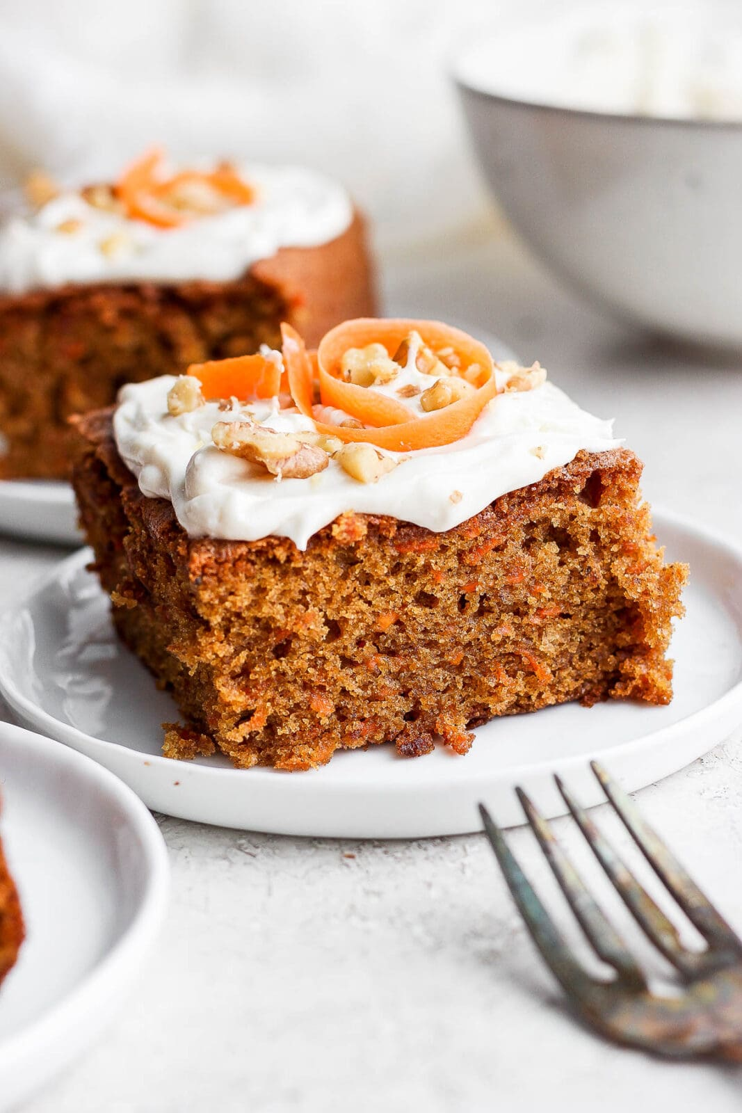 Plate with a slice of gluten free carrot cake with cream cheese frosting.