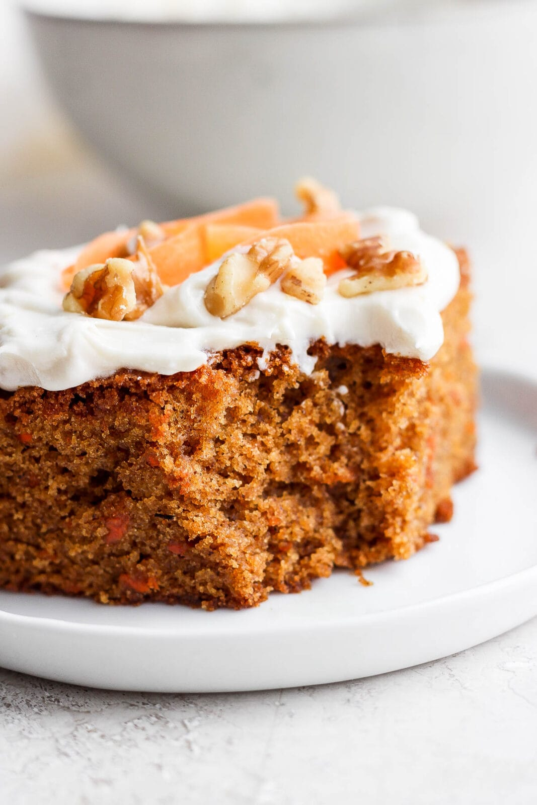 Slice of gluten free carrot cake with a bite out of it.