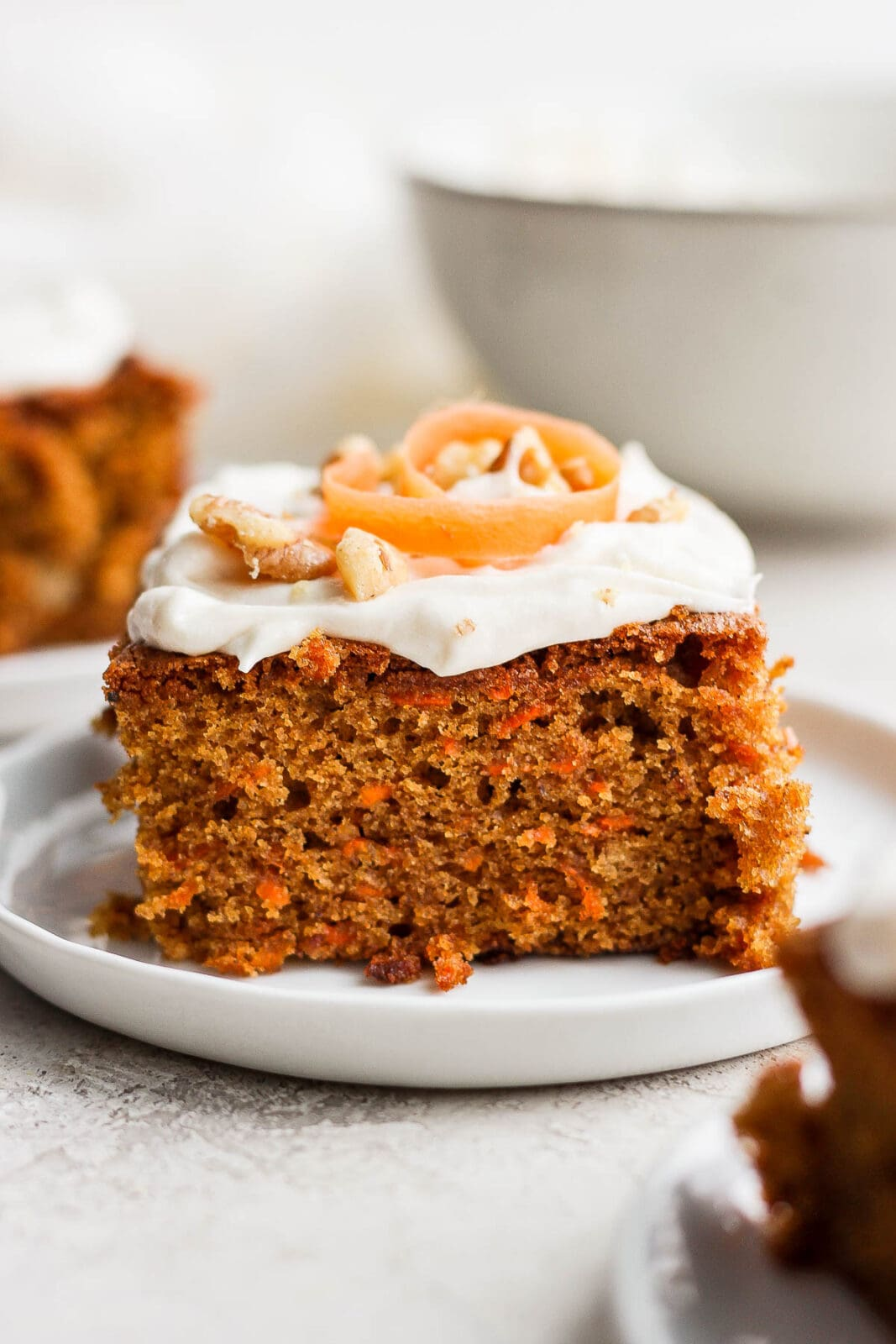 Slice of gluten free carrot cake on a plate with cream cheese frosting.