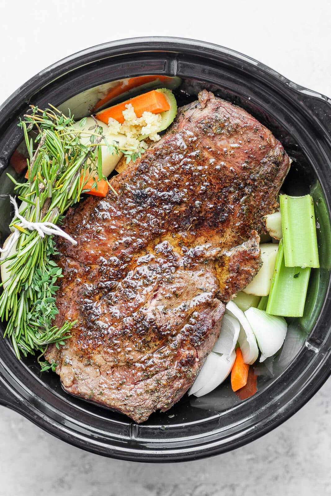 Slow cooker with pot roast, veggies, and herbs.