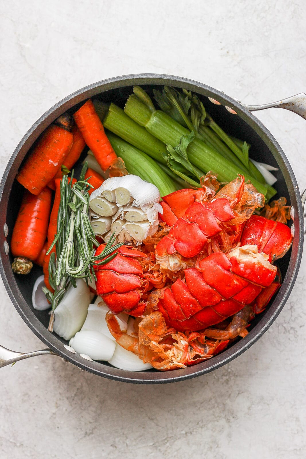 Dutch oven with seafood stock ingredients inside.