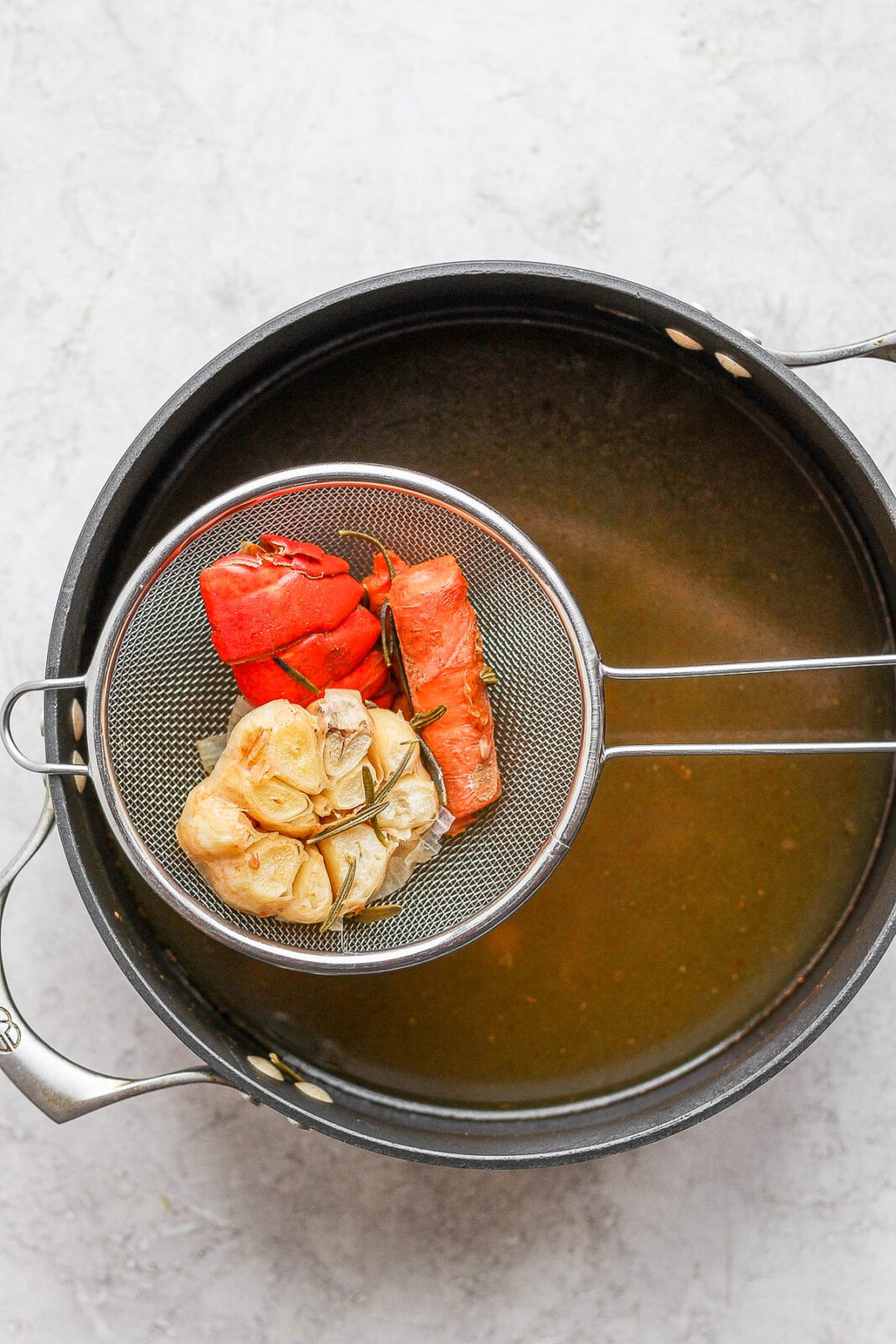 Image of straining large pieces out of the seafood stock.