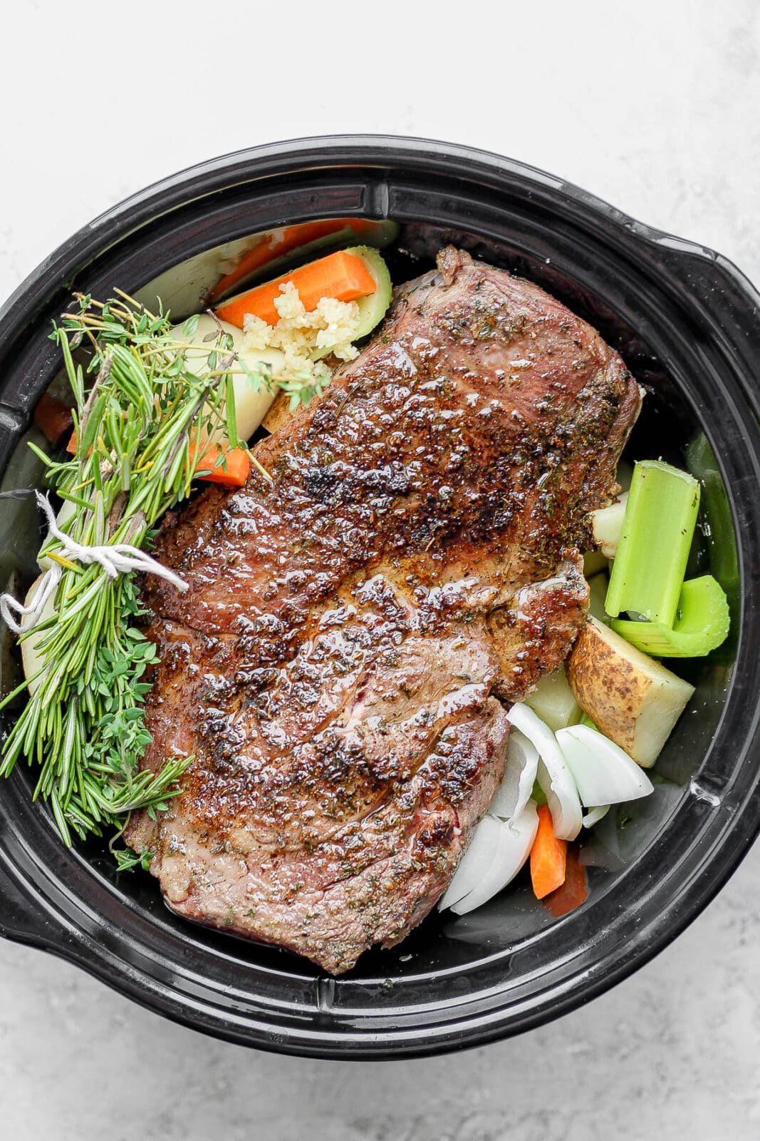 Slow cooker with beef roast, vegetables, and herbs.