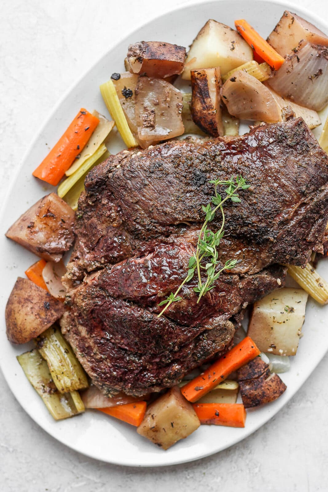 Plate with cooked slow cooker pot roast and vegetables.