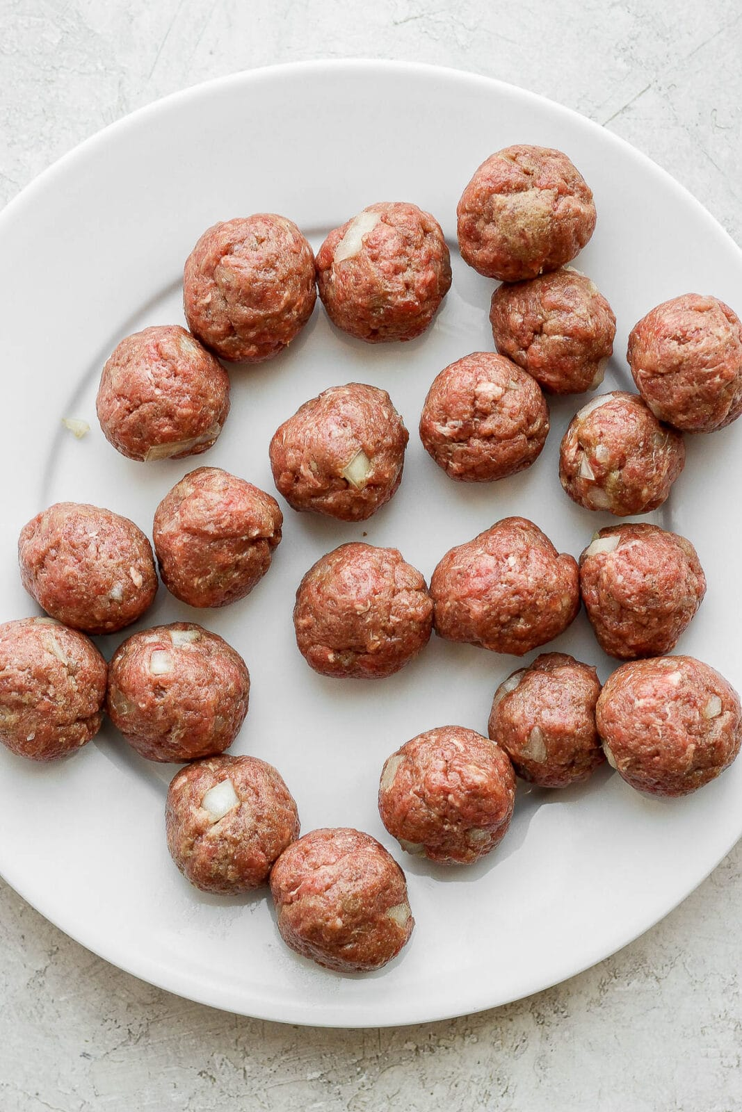 Plate of rolled meatballs before cooking.