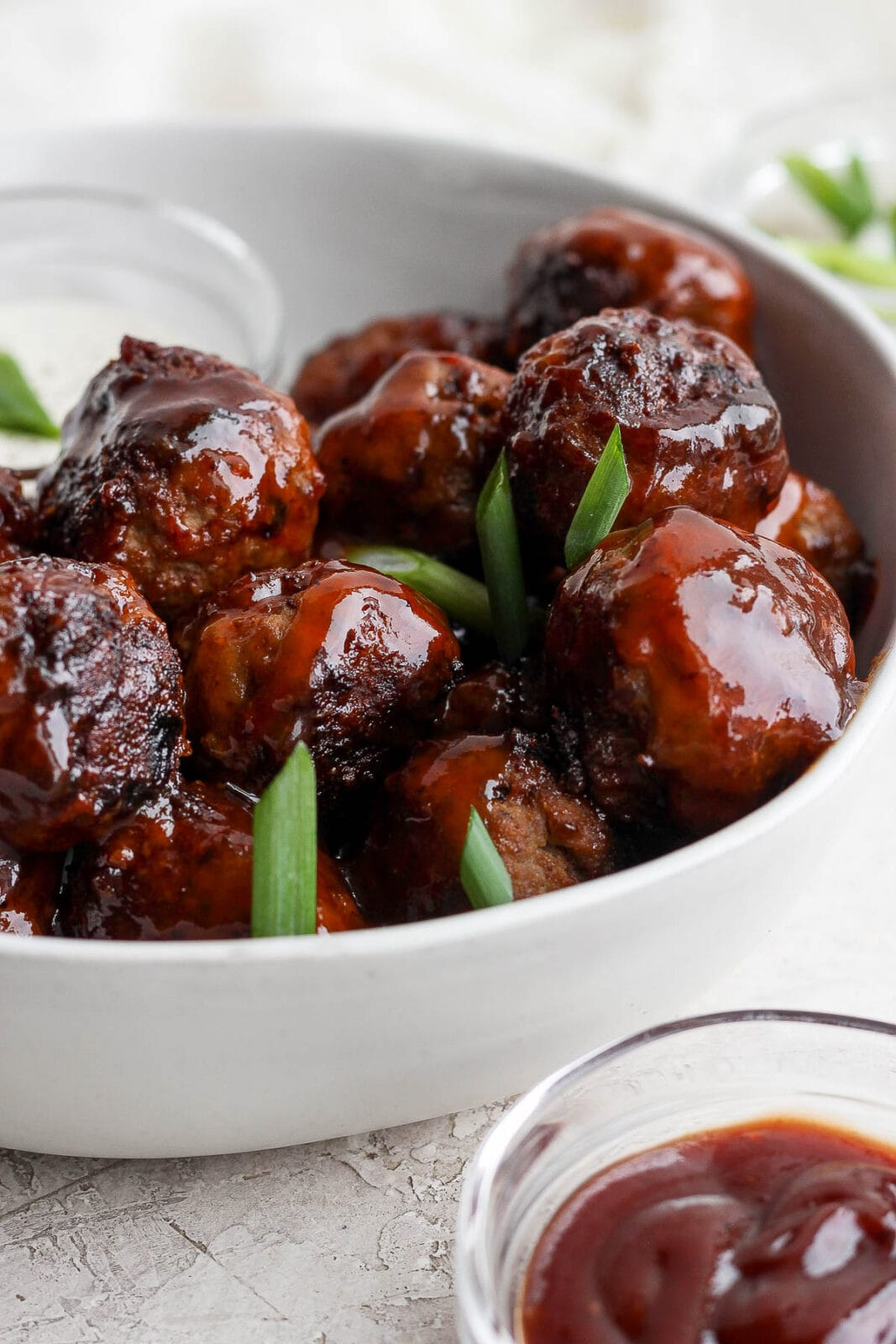 Bowl of BBQ meatballs with sliced green onions and dipping sauce.