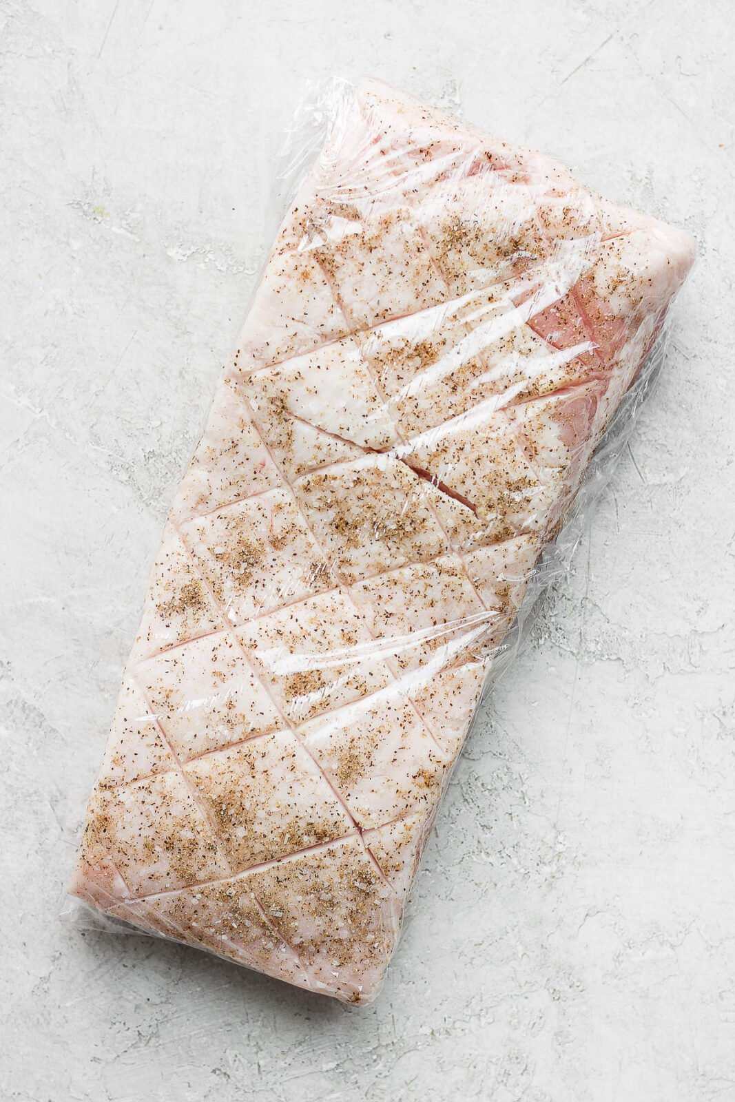 A piece of pork belly scored, rubbed with seasoning and wrapped plastic wrap.