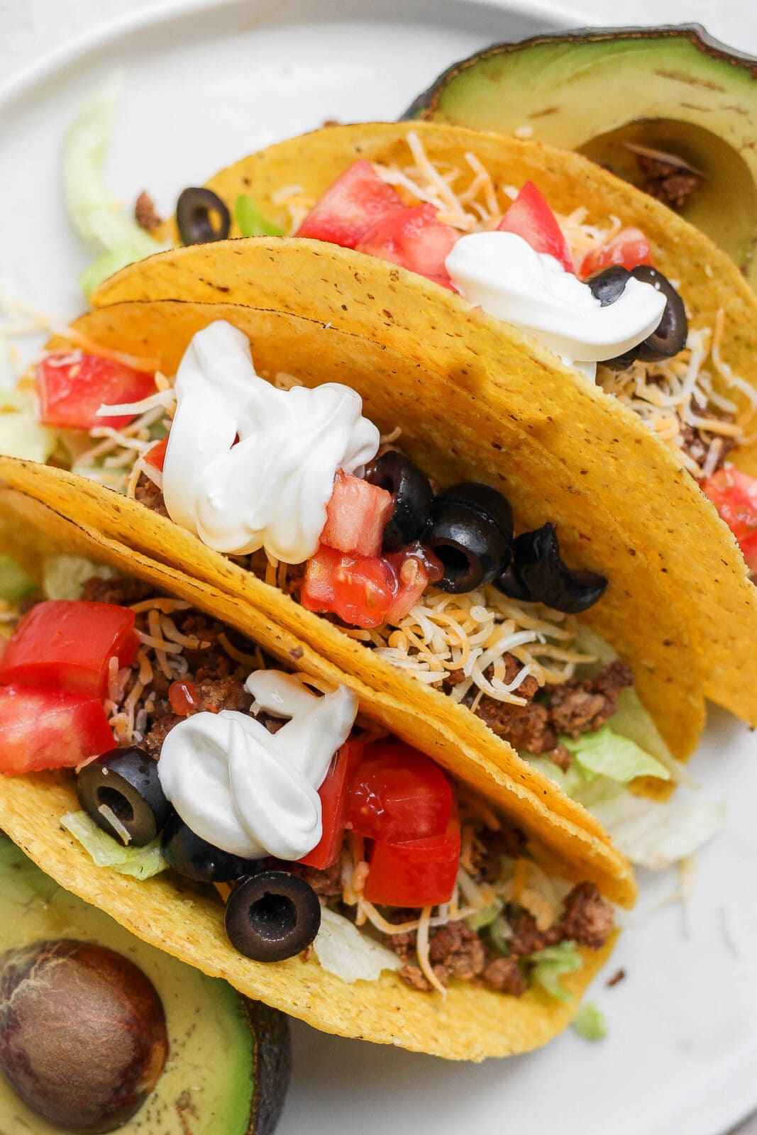 Plate with 3 homemade tacos in hard shells.