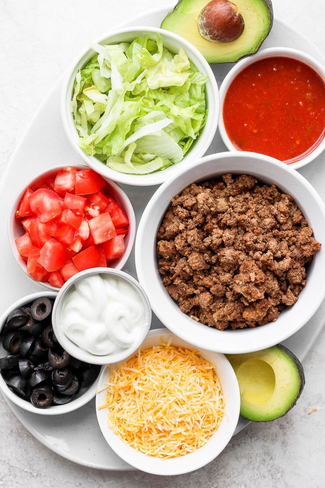 Large plate with several small bowls that each hold a different ingredient for tacos included cooked taco meat.
