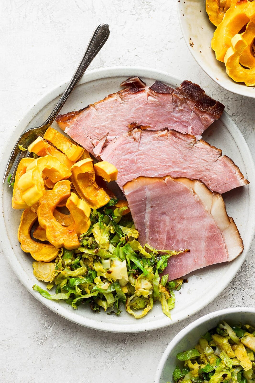Plate with slices of baked ham, squash, and shaved brussel sprouts.