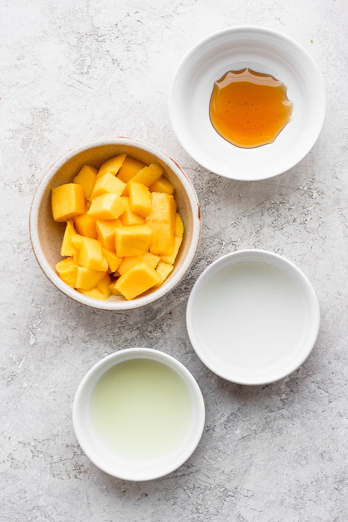 Ingredients for mango margaritas in small white bowls.
