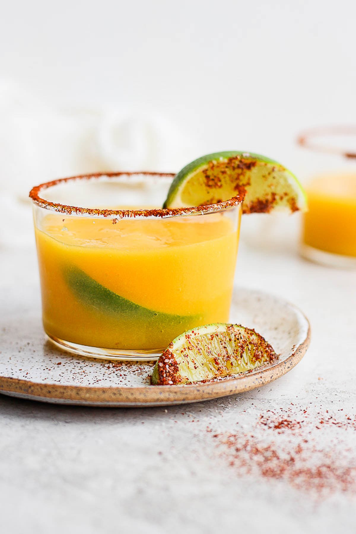 Mango Margarita in a glass with a chili lime rim and fresh lime.