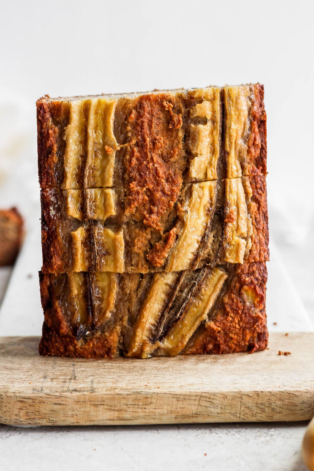 Slices of paleo banana bread stacked on a cutting board.