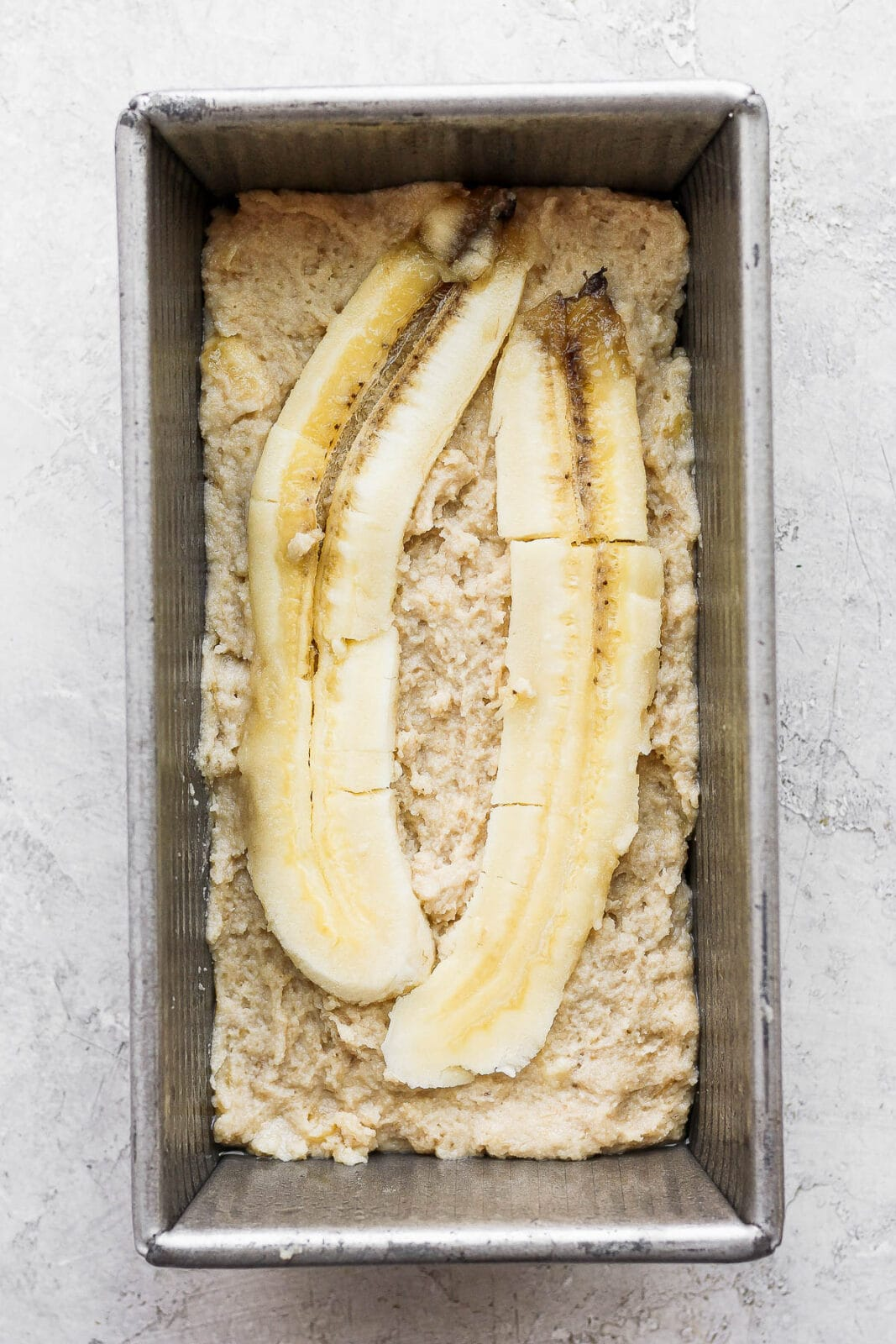 Paleo banana bread batter with a sliced banana on top for garnish in a loaf pan.