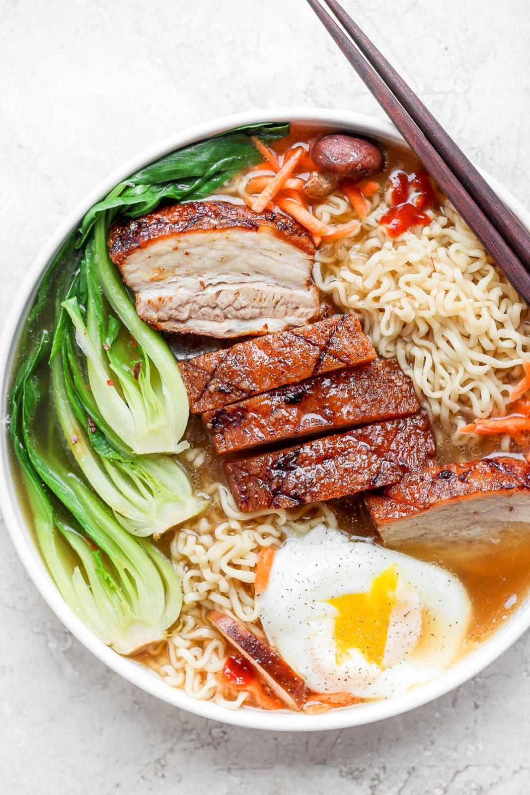 A bowl of pork belly ramen with chopsticks.