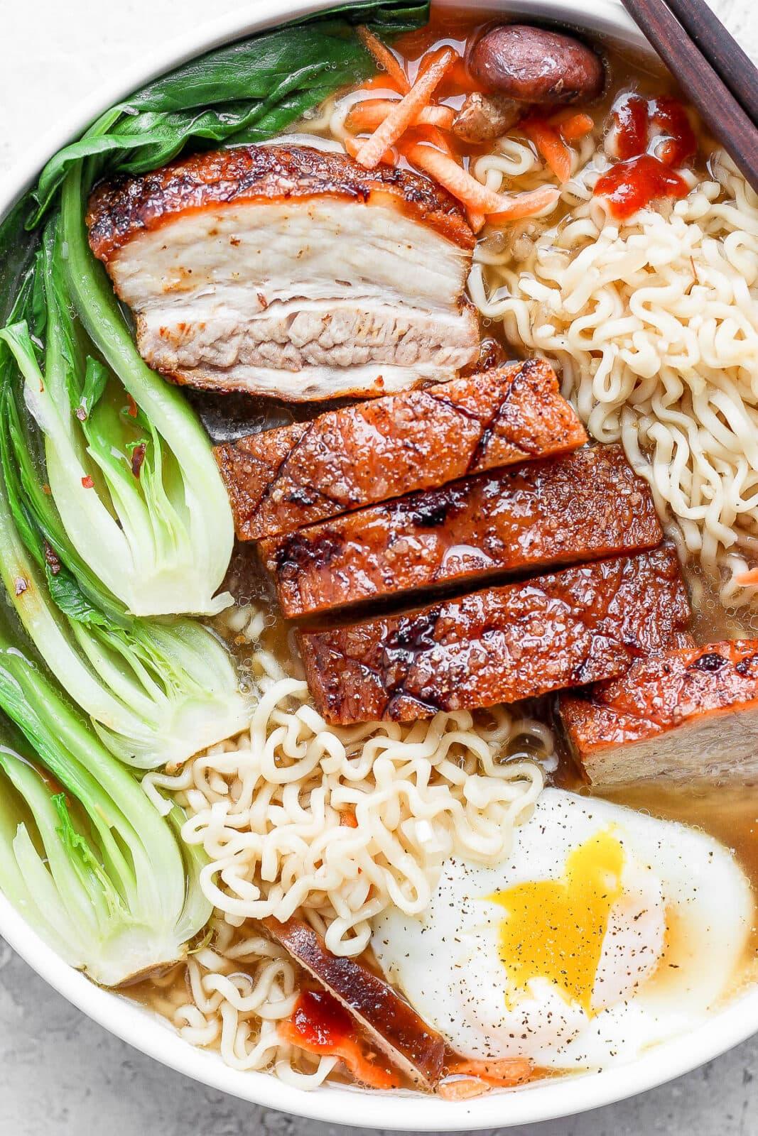 Pork belly ramen in a bowl with chopsticks.